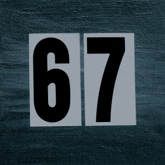 grey painted square background, in the center, large adhesive black numbers 6 and 7 almost filling the space. The numbers have a white rectangular background